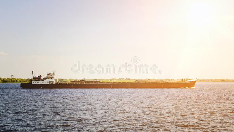 The barge floats along the river in the light of the setting sun. Beautiful view royalty free stock image