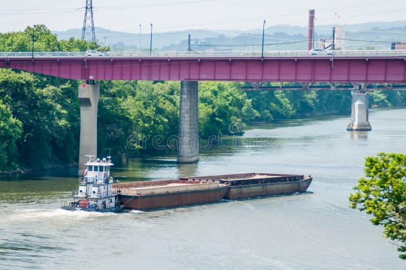 Barge ship moving on water towards bridge stock photography