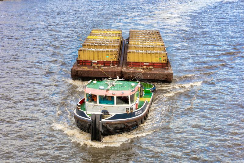 Barge towing containers on River Thames royalty free stock photography