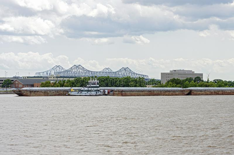 Barges and Tugboat on Mississippi River in New Orleans. Barges and tugboat on mississippi river at algiers point with crescent city connection bridge behind it royalty free stock photos
