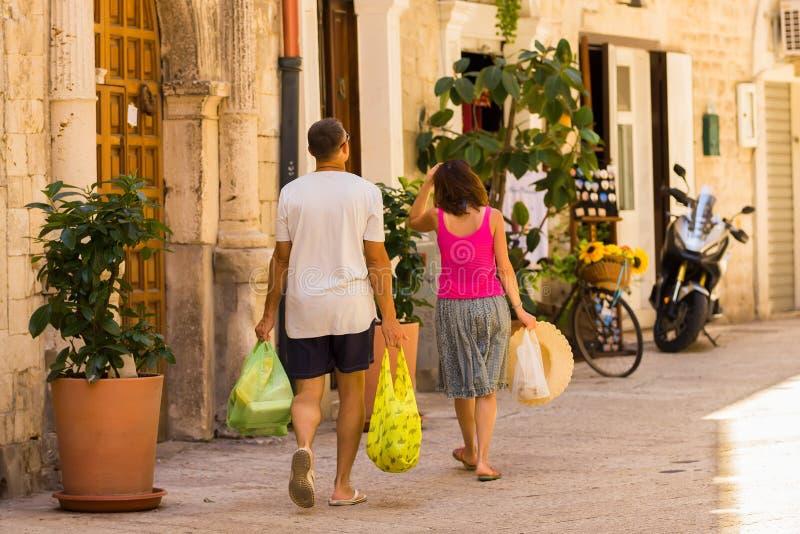 BARI, ITALIË - JULI 11, 2018, een man en een vrouw komen met aankopen, een scène vanaf het dagelijkse leven de straat van oud Bar royalty-vrije stock foto