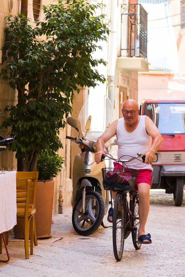 BARI ITALIEN - JULI 11, 2018, platser från livet av mitten av Bari: en gamal man som rider en cykel arkivfoto