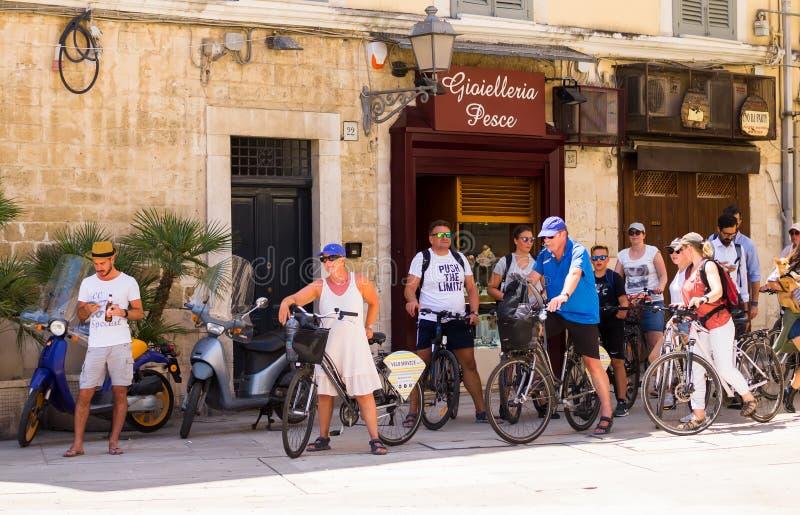 BARI ITALIEN - JULI 11, 2018, turister på cyklar på gatorna i mitten av Bari på en solig dag för varm sommar arkivbild