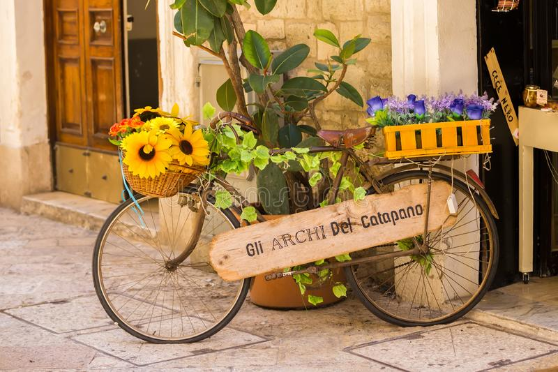 BARI, ITALY - JULY 11, 2018, View of a narrow street in the center of Bari. An old bicycle decorated with flowers outside a shop stock image