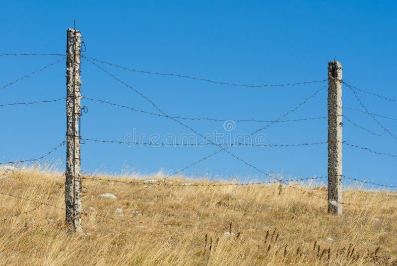 Bariera z drutem kolczastym przeciw niebieskiemu niebu obrazy stock