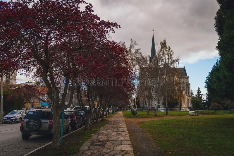 BARILOCHE, ARGENTINA, JUNE 18, 2019: perspective view of the colorful path with red trees beside to Nuestra Senora del Nahuel. Huapi Cathedral royalty free stock photography