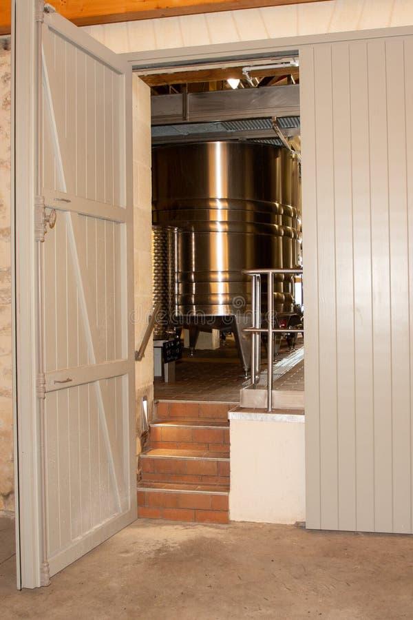 Barilotti di alluminio moderni dopo la porta di legno in cantina immagine stock