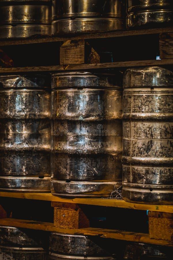 Barilotti di birra di alluminio brillanti impilati in una fabbrica di birra fotografie stock