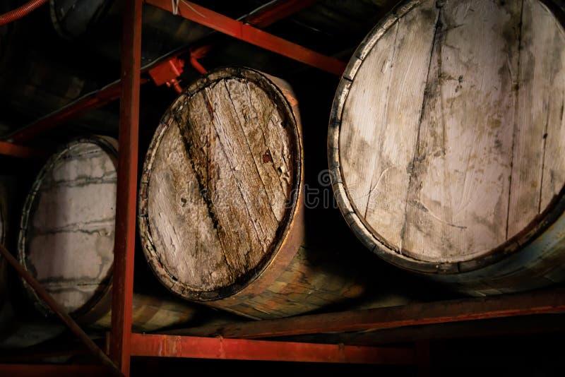 Barilotti di legno del whiskey o del rum impilati in un magazzino fotografia stock