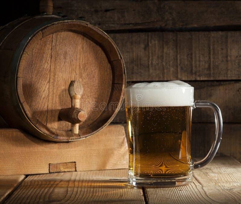 Barilotto di birra con la tazza di birra su fondo di legno immagine stock