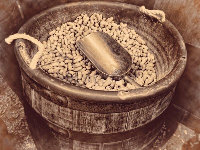Barilotto di legno delle arachidi pieno dei dadi e fondo d'annata del mestolo di retro fotografie stock libere da diritti