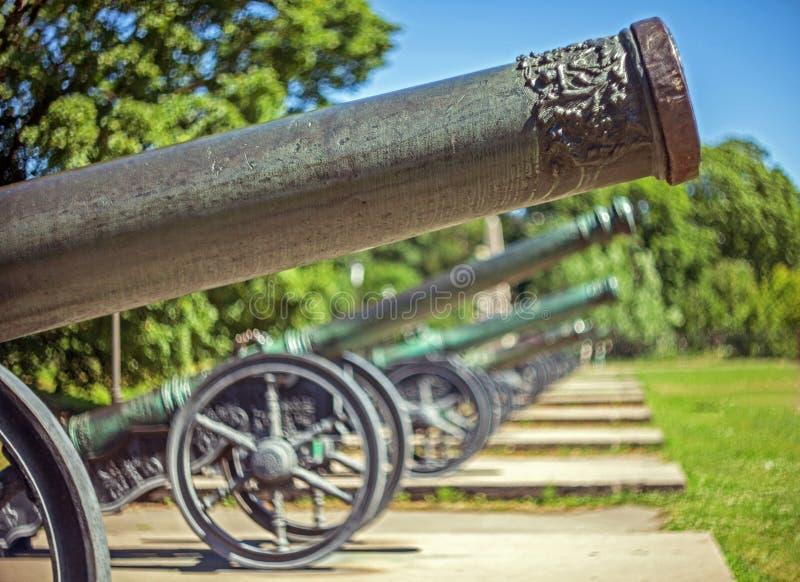 Barils de canons d'en cuivre de cru sur des roues et des chariots avec un fond brouillé photos stock