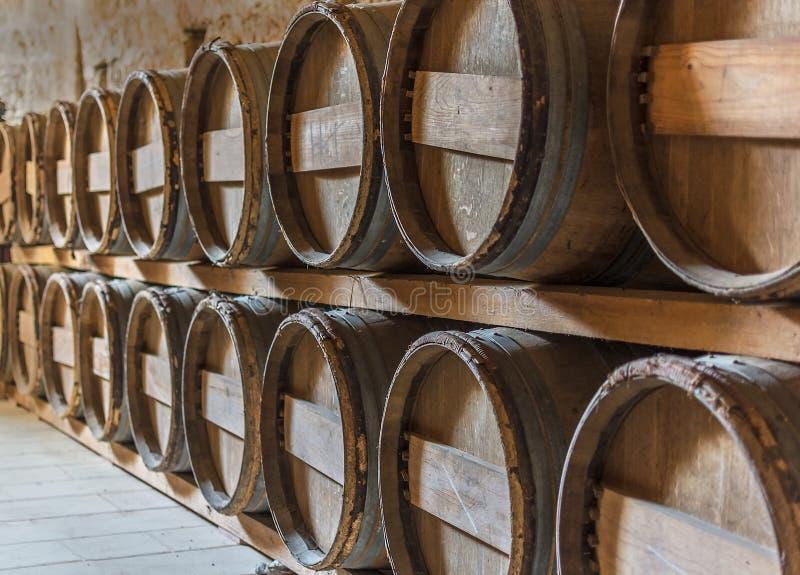 Barils de vin empilés dans les rangées dans la vin-chambre forte image libre de droits
