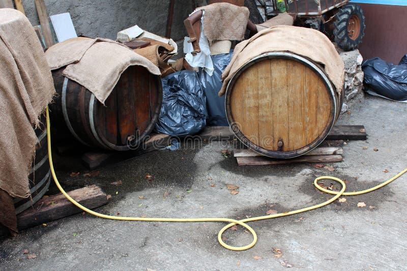 Barils de vin en bois étant préparés dans l'arrière-cour pavée pour la nouvelle saison entourée avec des sachets en plastique et  image stock