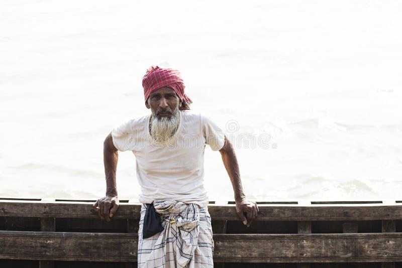 Barisal, Bangladesh, el 27 de febrero de 2017: Hombre mayor que presenta en el embarcadero imagen de archivo libre de regalías