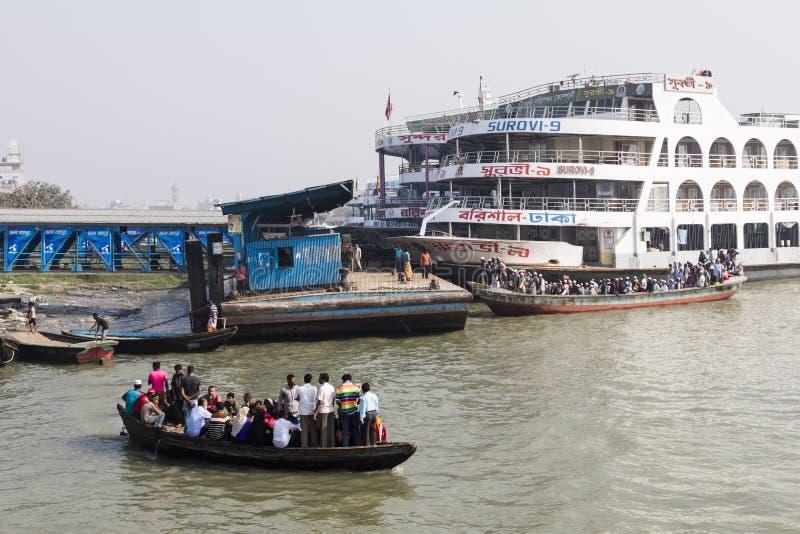 Barisal, Bangladesh, el 27 de febrero de 2017: El taxi apretado del agua transita en el puerto de Barisal delante de un transbord imagenes de archivo