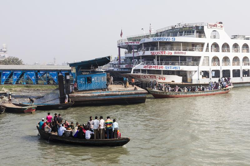 Barisal, Bangladesh, February 27 2017: Crowded water taxi transits in the port of Barisal in front of a passenger ferry. In Bangladesh stock images