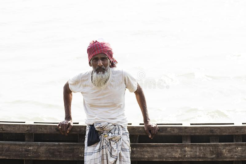 Barisal, Bangladesh, February 27 2017: Senior man posing at the pier. Barisal, Bangladesh, February 27 2017: Senior man posing at the port of Barisal in his boat royalty free stock image