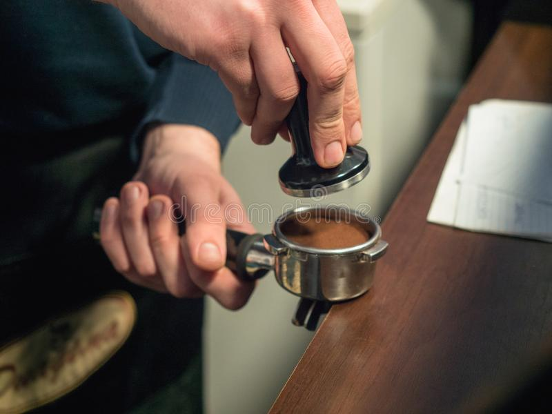 Barista在与软的焦点的被弄脏的背景组成咖啡,关闭, 侍酒者的手,在的被按的咖啡 免版税库存照片