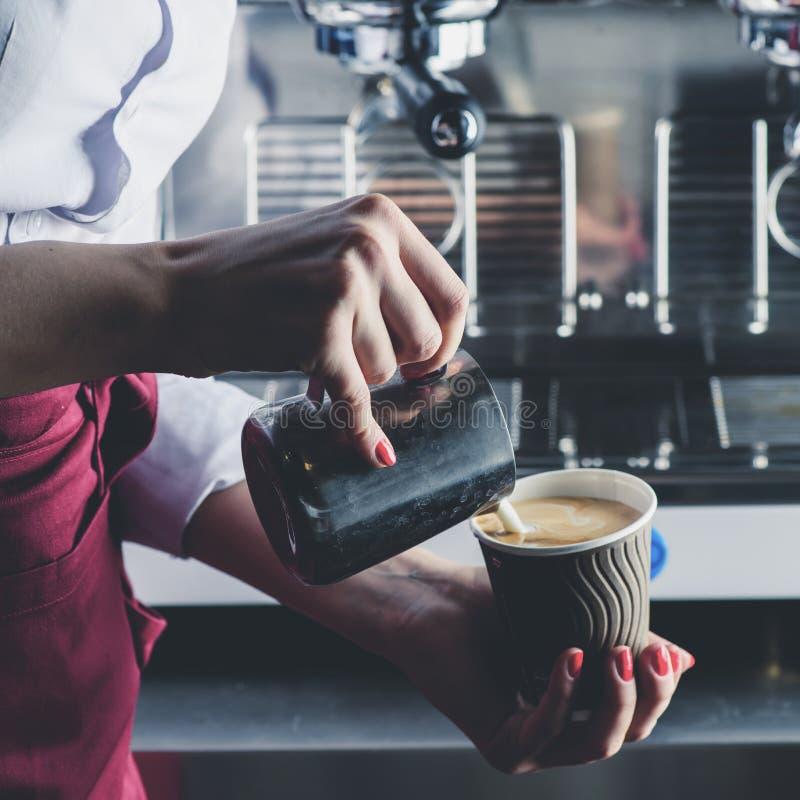 Barista女孩倾吐的牛奶到咖啡里 做cappucc的过程 免版税库存照片
