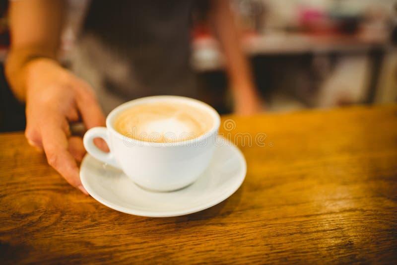 barista服务心脏形状泡沫的咖啡的中央部位在咖啡馆的 图库摄影