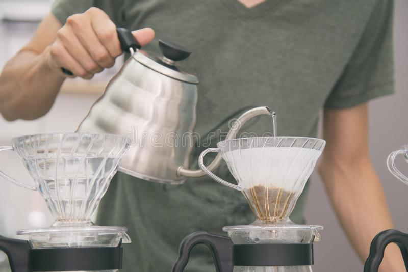 barista滴水咖啡,在咖啡渣的Barista倾吐的面汤的手与过滤器 免版税库存照片