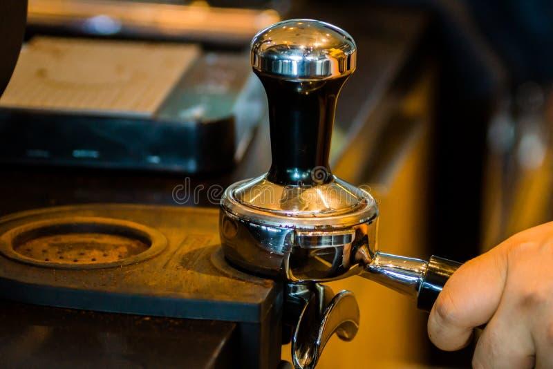 Barista砸紧在一家现代咖啡店的咖啡渣 库存图片