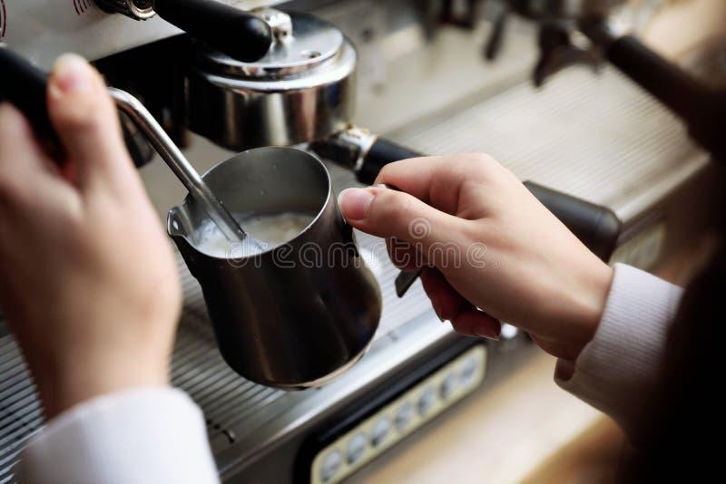 Barista που βράζει το γάλα που χρησιμοποιεί στον ατμό τη σύγχρονη μηχανή καφέ στοκ φωτογραφία με δικαίωμα ελεύθερης χρήσης