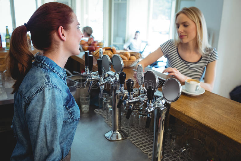 Barista που μιλά με τον πελάτη στον καφέ στοκ φωτογραφία