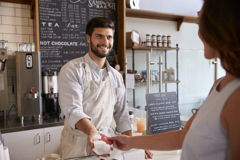 Barista που παίρνει την πληρωμή καρτών από έναν πελάτη σε μια καφετερία στοκ εικόνες