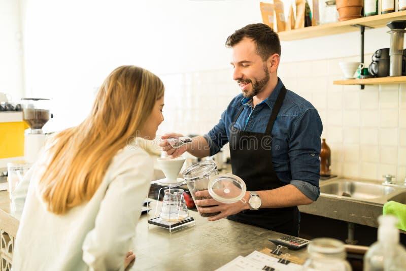 Barista που παρουσιάζει σιτάρια καφέ στον πελάτη στοκ φωτογραφία