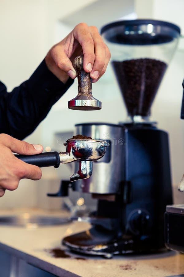 Barista που πιέζει τους φρέσκους λόγους καφέ στοκ φωτογραφία με δικαίωμα ελεύθερης χρήσης