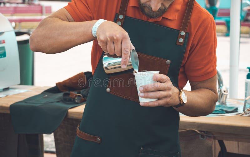 Barista που προετοιμάζει το φλιτζάνι του καφέ για τον πελάτη υπαίθριο στοκ εικόνες