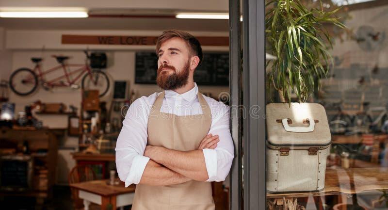 Barista που στέκεται στην πόρτα ενός καφέ στοκ εικόνα
