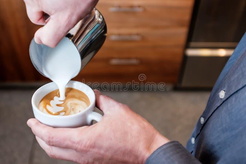 Barista που χύνει το βρασμένο στον ατμό γάλα στο φλυτζάνι καφέ που κάνει latte την τέχνη στοκ εικόνες