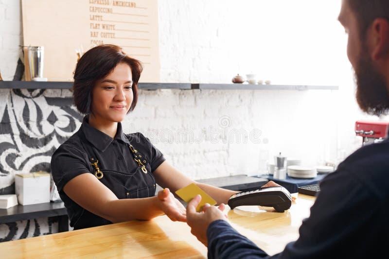Barista χαμόγελου που παίρνει την πληρωμή από τον πελάτη στο μετρητή μιας καφετερίας στοκ εικόνες με δικαίωμα ελεύθερης χρήσης