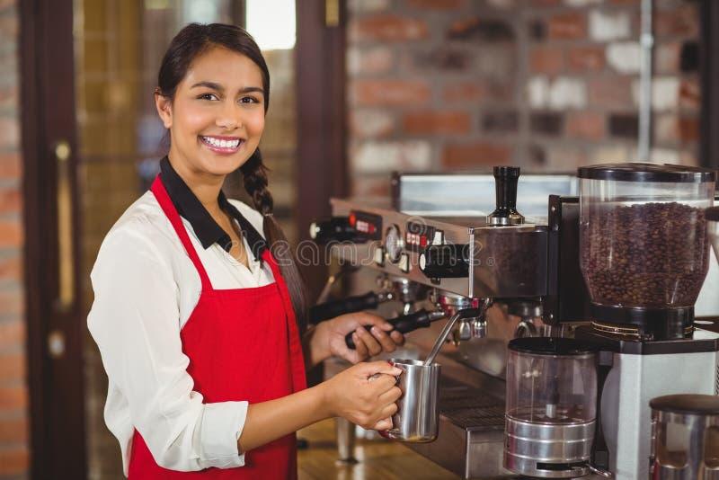 Barista χαμόγελου που βράζει το γάλα στον ατμό στη μηχανή καφέ στοκ εικόνα με δικαίωμα ελεύθερης χρήσης