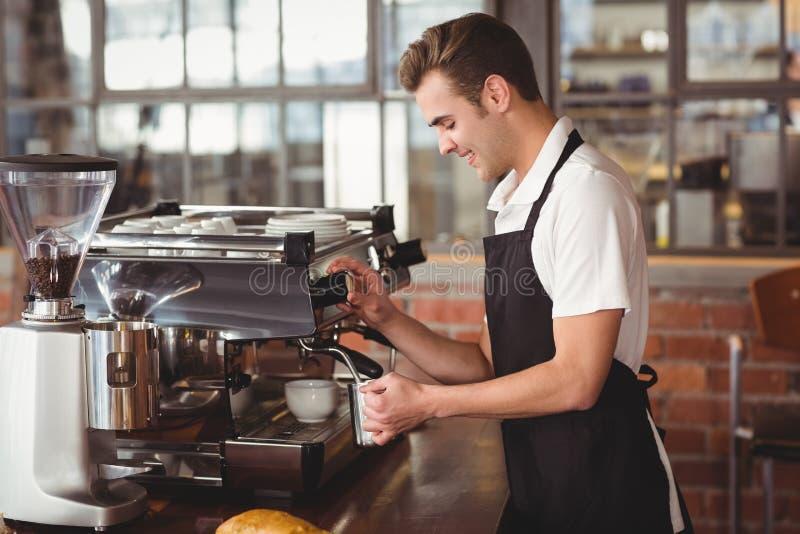 Barista χαμόγελου που βράζει το γάλα στον ατμό στη μηχανή καφέ στοκ εικόνες με δικαίωμα ελεύθερης χρήσης