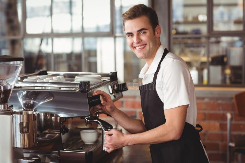 Barista χαμόγελου που βράζει το γάλα στον ατμό στη μηχανή καφέ στοκ φωτογραφία