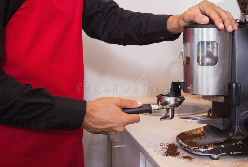 Barista χρησιμοποιώντας το μύλο καφέ για να αλέσει τα φασόλια καφέ στοκ εικόνα