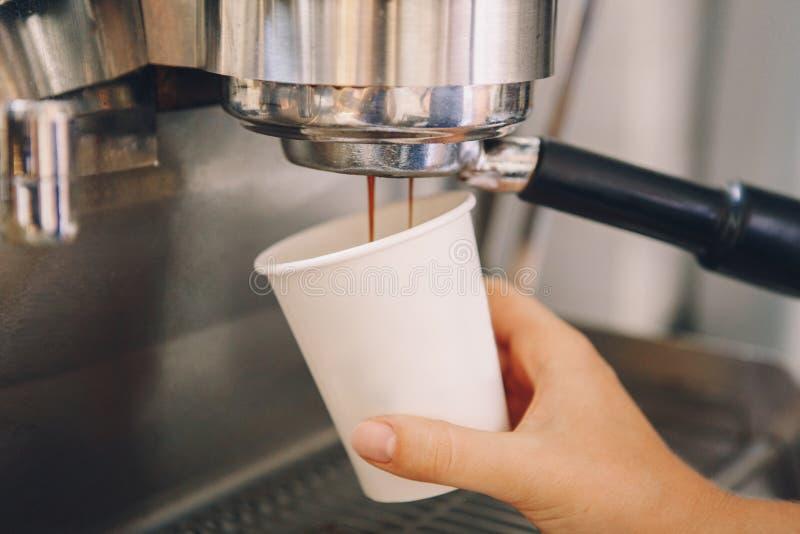 Barista вручает держать бумажный стаканчик делая кофе используя машину кофе стоковое фото