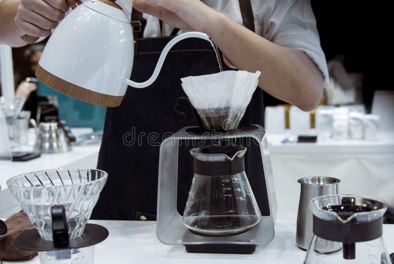 Barista делая кофе, кофе потека Barista лить в стекло стоковое фото