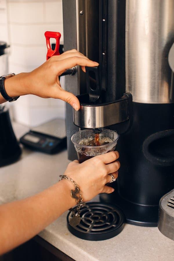 Barista женщины вручает делать лить кофе от машины кофе в пластичной прозрачной чашке стоковые фотографии rf