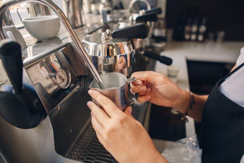 Barista женщины вручает делать лить кофе от машины кофе в пластичной прозрачной чашке стоковые изображения