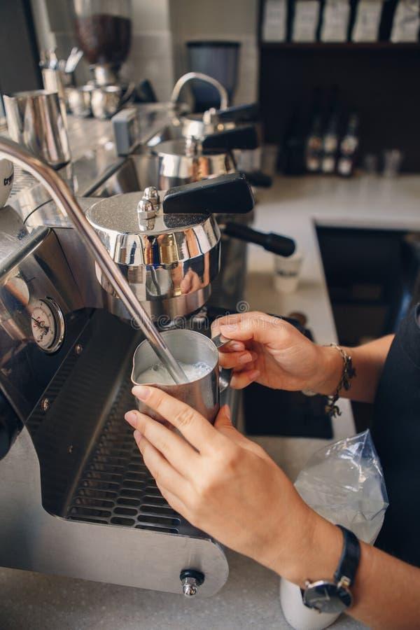 Barista женщины вручает держать кувшин молока для делать кофе используя машину кофе стоковые фото