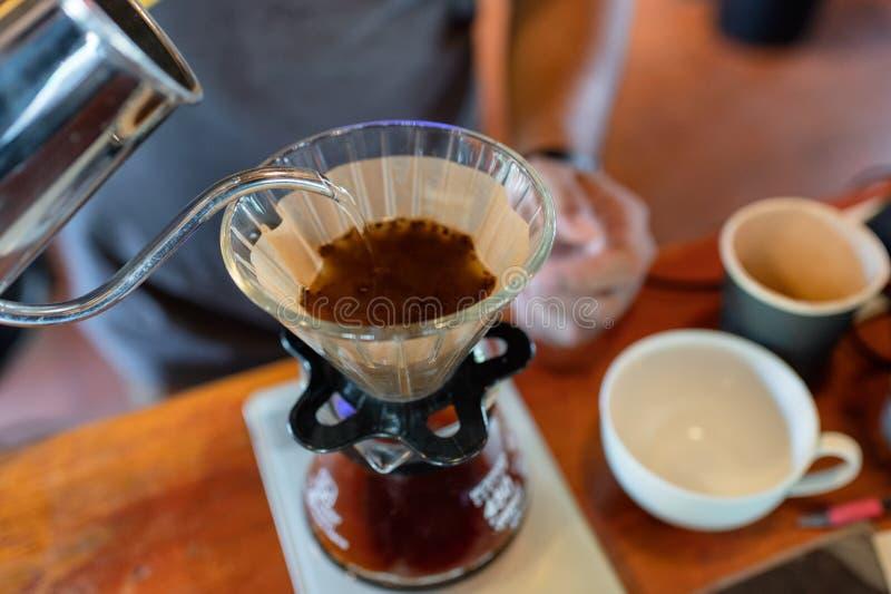 Barista лить горячую воду в бумажном фильтре с кофе молотилки стоковая фотография rf