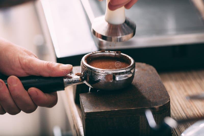 Barista отжимая кофе в держателе машины стоковая фотография