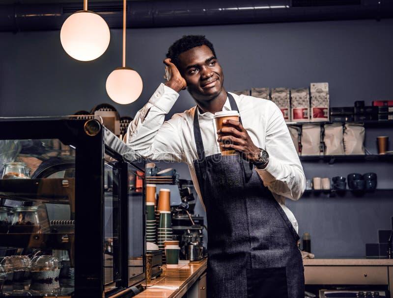Barista africano que sostiene una taza con café mientras que se inclina en un contador en una cafetería y mira de lado imagen de archivo libre de regalías