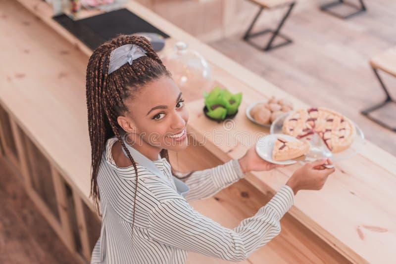 Barista afro-americano de sorriso que coloca uma parte de torta imagens de stock royalty free