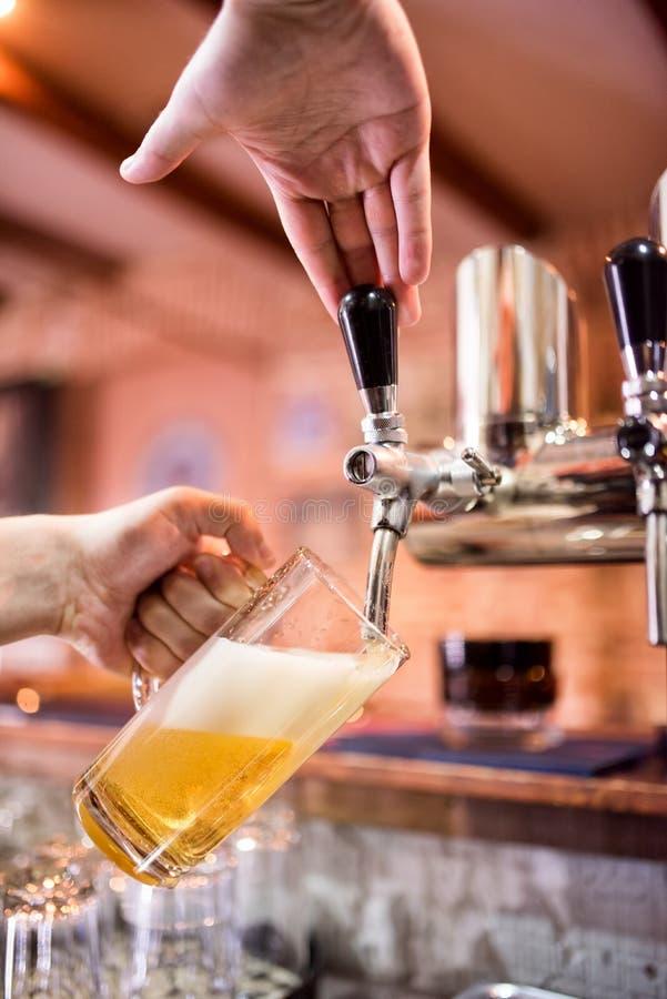 Barista alla lager di versamento del pub o dei bistrot ed alla birra non filtrata in vetro fotografia stock